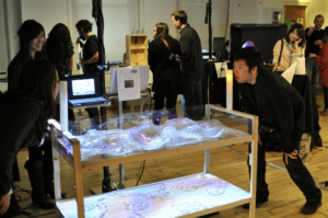 Photo of two people facing each other across a table with a model of a landscape on it. They look at each other and blow into sensors to affect the image projected on the landscape.