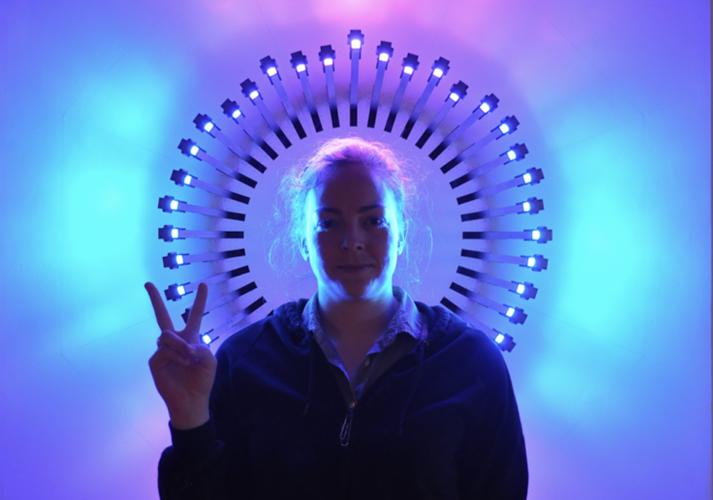 Photo of a woman in front of a changing light field. The field is created by a circular arrangement of moving rods, each of which has a light on the end