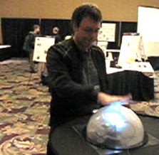 Photo of a man tapping a large lit dome on a tabletop.