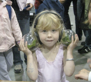 Photo of a young girl wearing a pair of headphones made of glass globes. Each globe carries a nest of crickets.