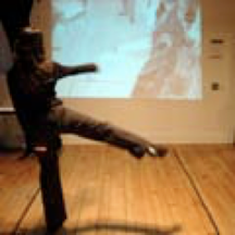 Photo of a dancer dancing in front of a screen. The graphics on the screen appear to change with her movement.