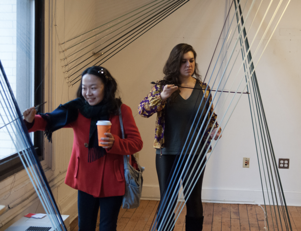 Photo of a series of strings that connect the floor, walls, and ceilings of a room. Participants are plucking the strings and drawing a violin bow across them.