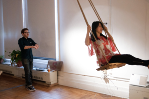Photo of a woman swinging on a swing suspended from a ceiling.